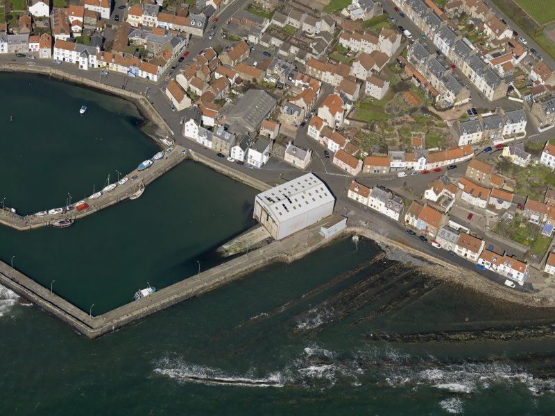 Oblique aerial view centred on the boathouse/boatshed with the harbour adjacent, taken from the SE.