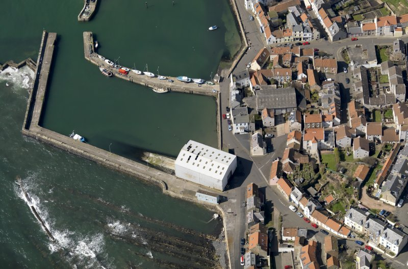 Oblique aerial view centred on the boathouse/boatshed with the harbour adjacent, taken from the E.