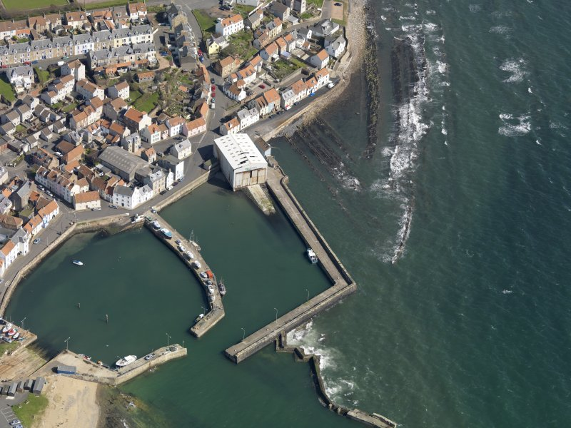 Oblique aerial view centred on the boathouse/boatshed with the harbour adjacent, taken from the SSW.