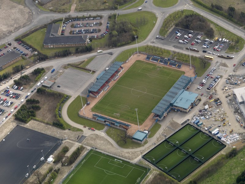 Oblique aerial view centred on the football ground, taken from the NW.
