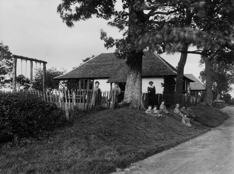 View of single-storey building on the Montgreenan House estate, showing children sitting outside.