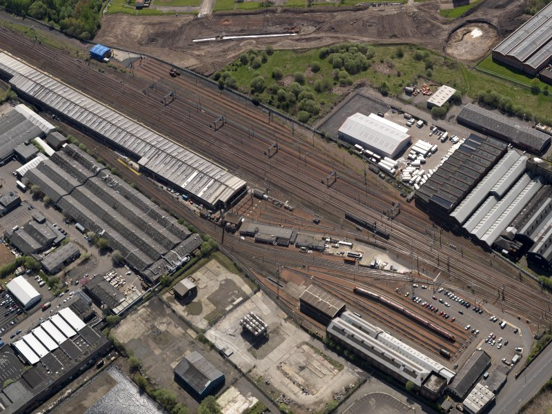 Oblique aerial view centred on the surviving section of the original motive power depot with the modern traction depot adjacent, taken from the NW.
