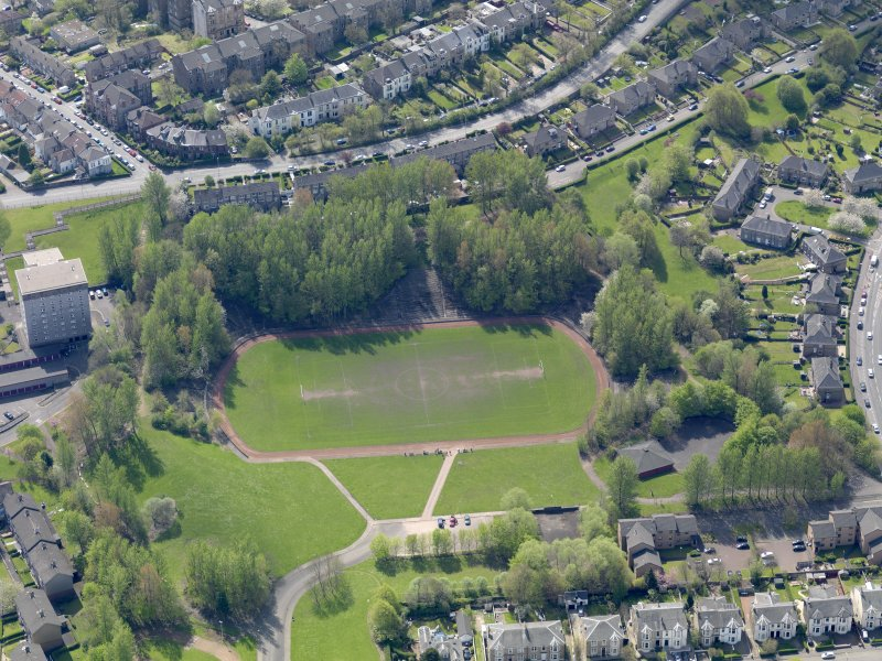 Oblique aerial view centred on the remains of the football ground, taken from the N.
