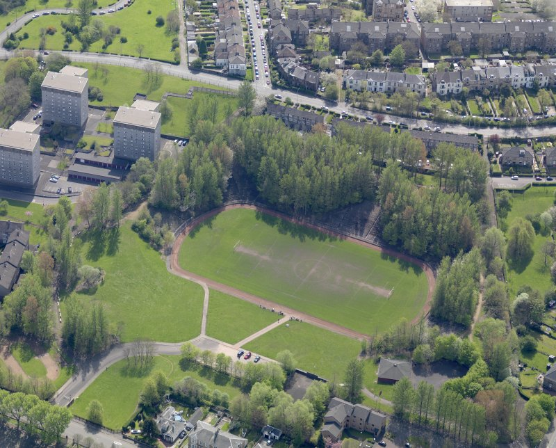 Oblique aerial view centred on the remains of the football ground, taken from the NW.