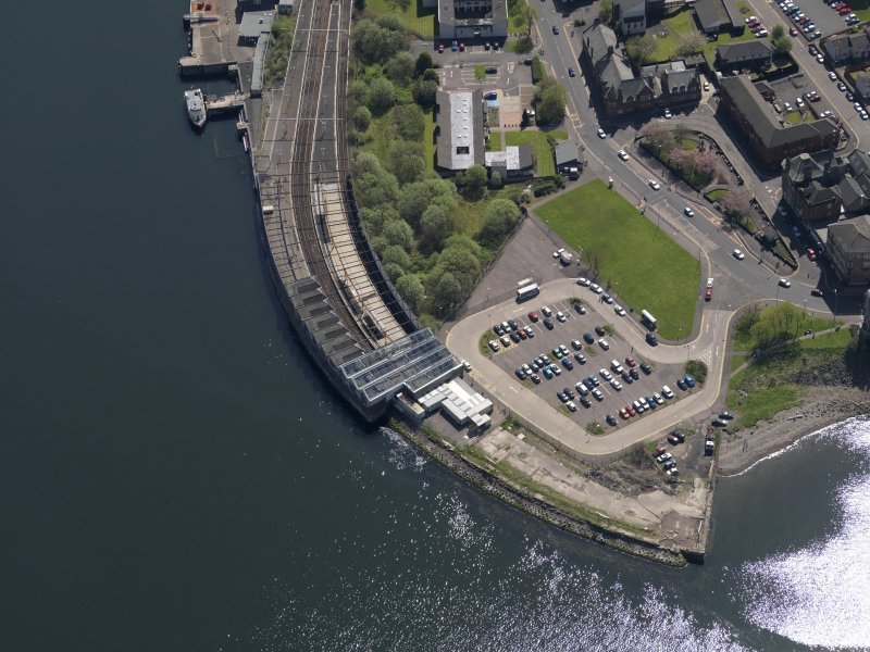 Oblique aerial view centred on the railway terminus and pier, taken from the N.