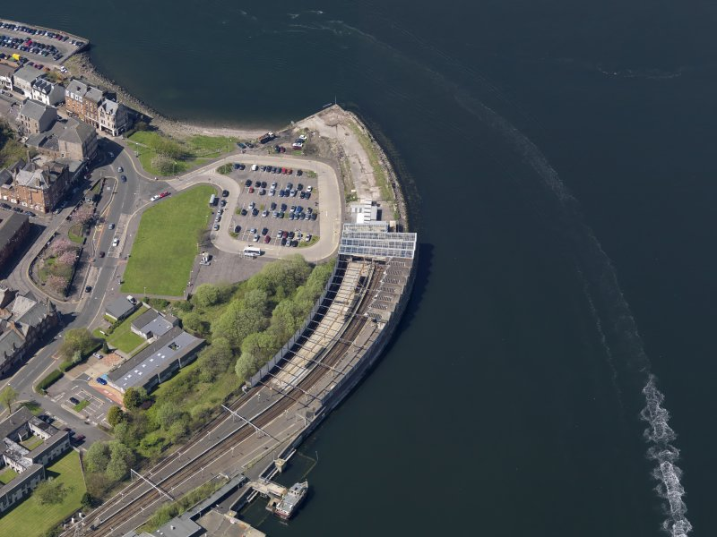 Oblique aerial view centred on the railway terminus and pier, taken from the SE.
