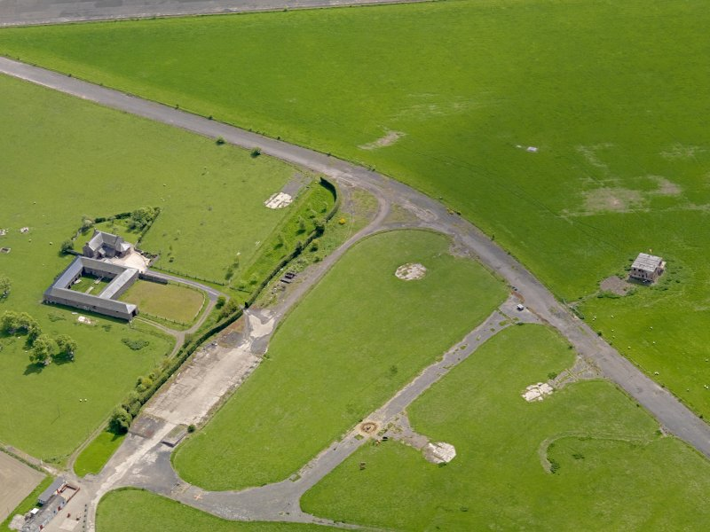 Oblique aerial view centred on the dispersal area with the control tower and farmsteading adjacent, taken from the N.