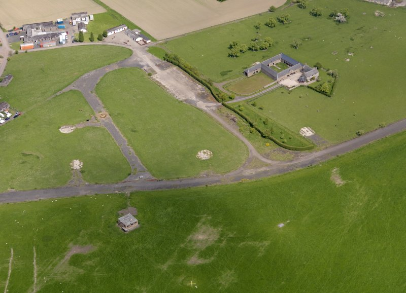 Oblique aerial view centred on the control tower with the dispersal area and farmsteading adjacent, taken from the WNW.
