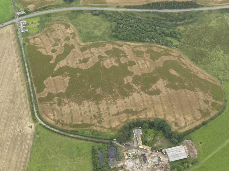 Oblique aerial view of the cropmarks of the pit defined avenue and cursus and the barrow at Kirkmabreck, taken from the SW.