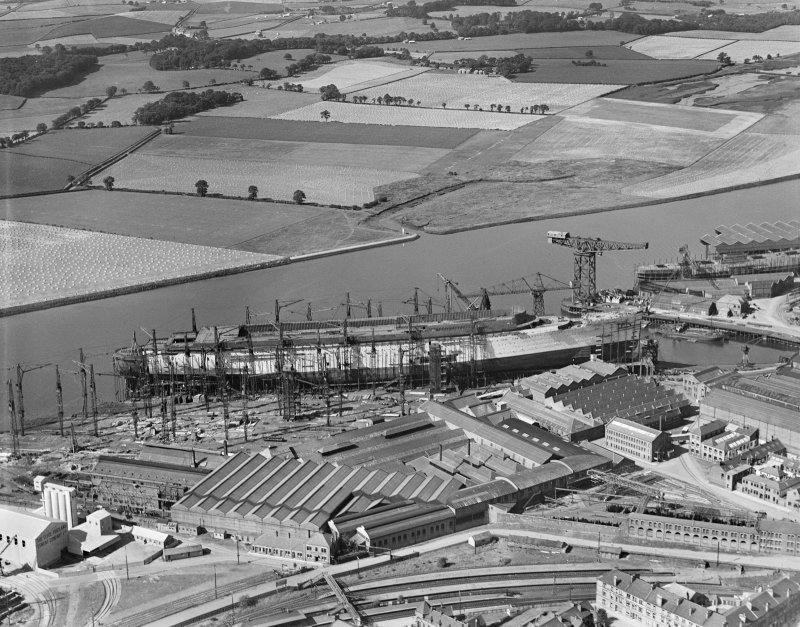 RMS Queen Mary, under construction in John Brown's shipyard, Clydebank. Oblique aerial view of the liner from SW.
