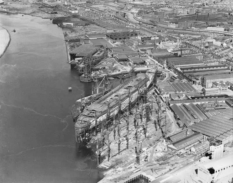 RMS Queen Mary, under construction in John Brown's shipyard, Clydebank. Oblique aerial view of the liner, from NE.