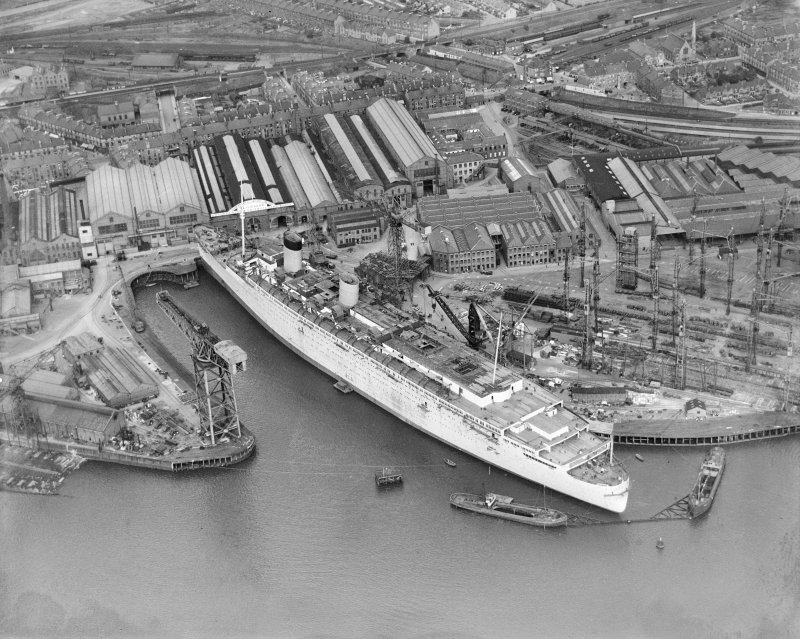 RMS Queen Mary, under construction in John Brown's shipyard, Clydebank. Oblique aerial view of the liner, from SW.