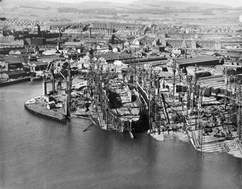 RMS Queen Elizabeth, under construction in John Brown's shipyard, Clydebank. Oblique aerial view of the liner, from S.