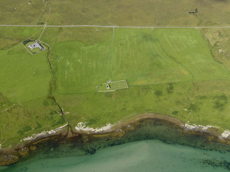 Oblique aerial view centred on the ruins of the chapel and the burial ground at Kilnave, Islay, taken from the ESE.