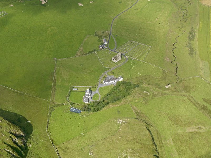 Oblique aerial view centred on the church, cemetery, manse and house at Kilchoman, Islay, taken from the SE.