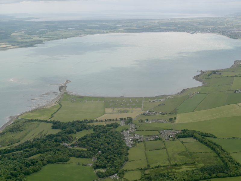 General oblique aerial view looking across Loch Ryan with the village and the remains of the sea plane base in the foreground, taken from the NNE.