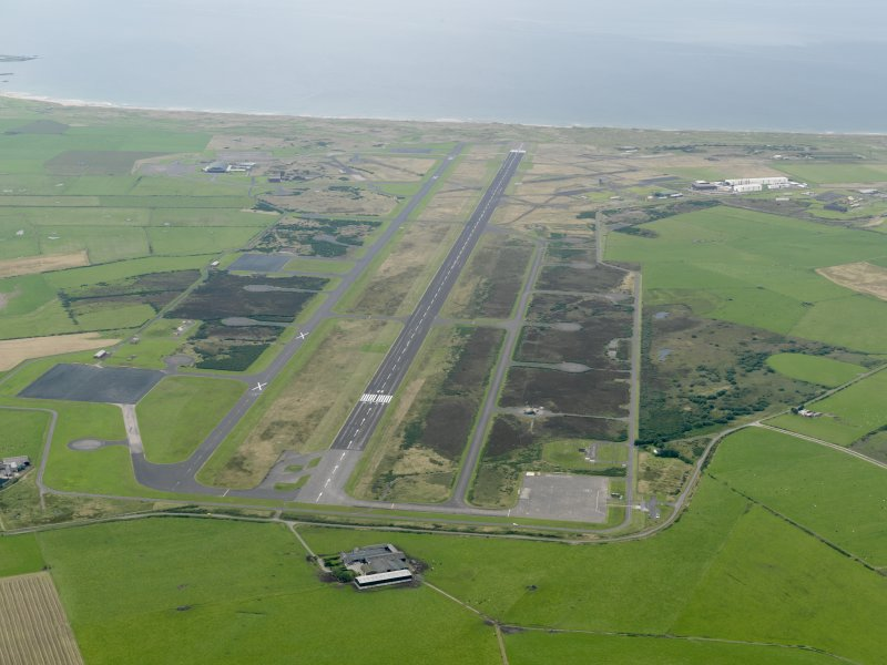 General oblique aerial view looking down the main runway at Machrihanish Airfield, taken from the E.