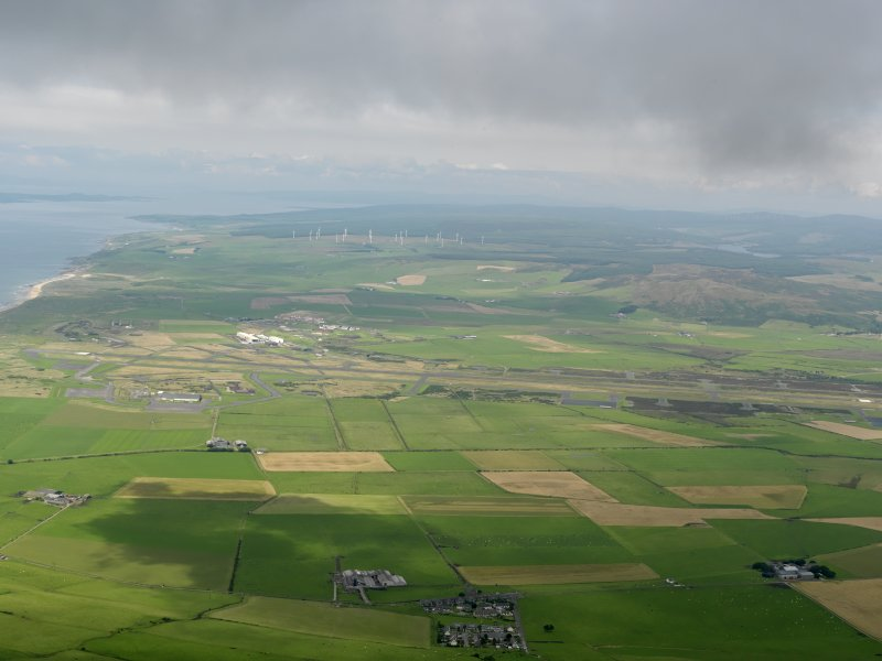 General oblique aerial view looking across Machrihanish Airfield towards the windfarm, taken from the SSW.