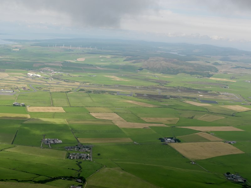 General oblique aerial view looking across Machrihanish Airfield towards the windfarm, taken from the SSE.