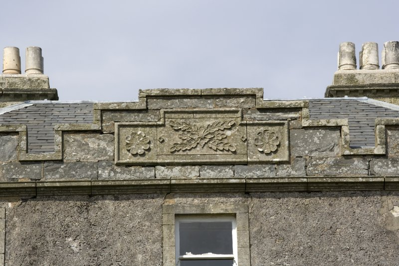 South front.  Detail of carved panel on parapet.