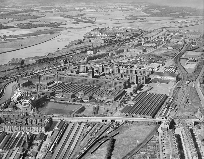 Oblique aerial view centred on Singer Sewing Factory, Clydebank, with the railway station adjacent with John Brown's shipbuilding yard in the background, taken from the E.