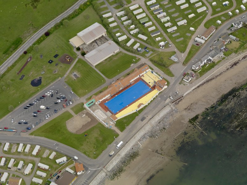 Oblique aerial view centred on the open air swimming pool with the Leisure Centre adjacent, taken from the S.