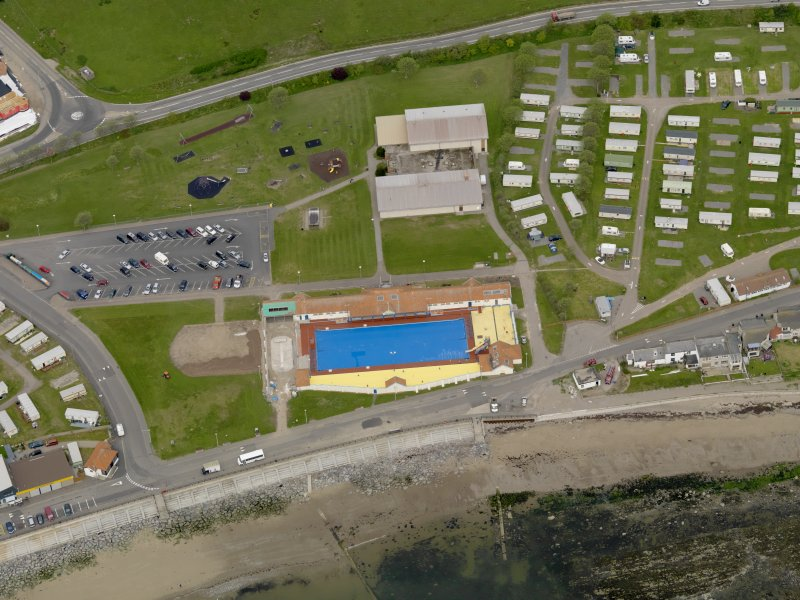 Oblique aerial view centred on the open air swimming pool with the Leisure Centre adjacent, taken from the SE.