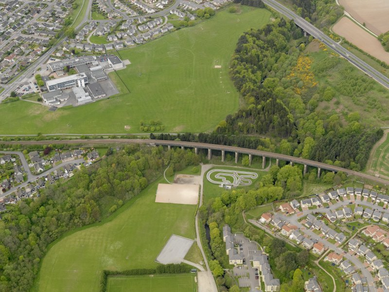 Oblique aerial view centred on the railway viaduct with the school adjacent, taken from the SE.