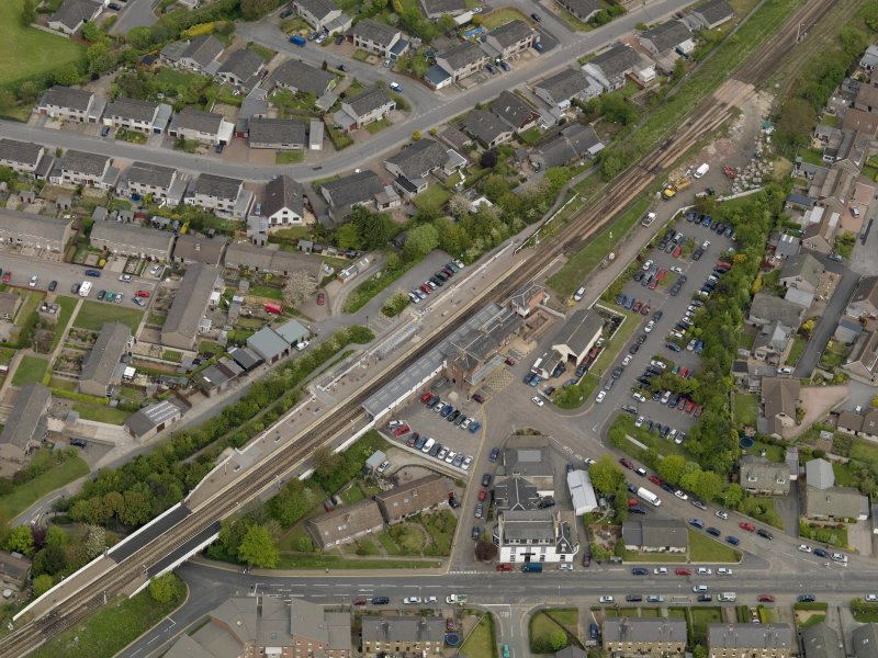 Oblique aerial view centred on the railway station with the Station Hotel adjacent, taken from the S.