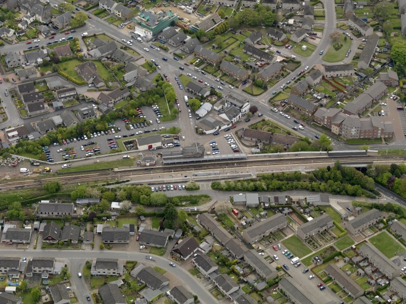 Oblique aerial view centred on the railway station with the Station Hotel adjacent, taken from the NW.