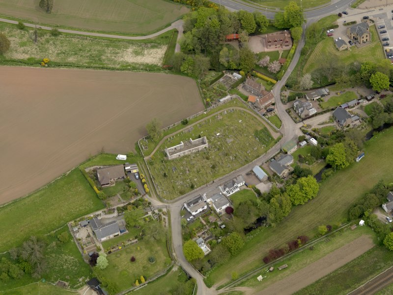 Oblique aerial view centred on the church with the graveyard adjacent, taken from the SSW.
