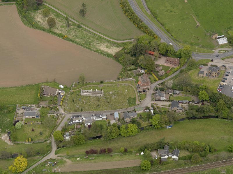 Oblique aerial view centred on the church with the graveyard adjacent, taken from the S.