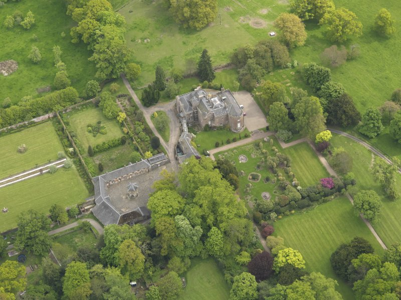 Oblique aerial view of the tower house with the gardens and stables adjacent, taken from the WNW.