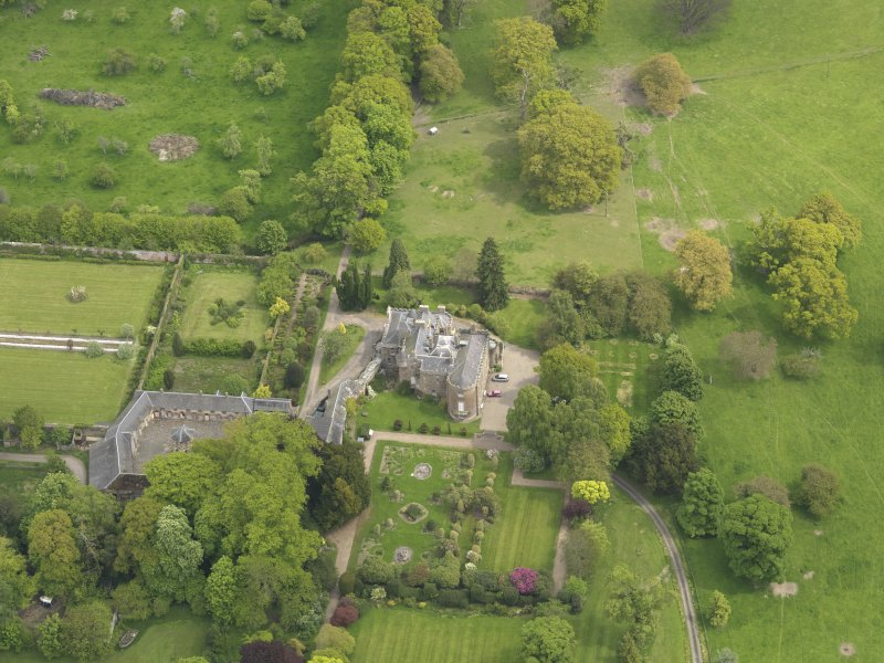 Oblique aerial view of the tower house with the gardens and stables adjacent, taken from the WSW.