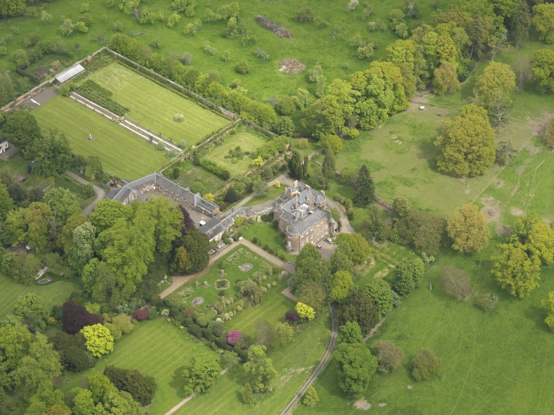 Oblique aerial view of the tower house with the gardens and stables adjacent, taken from the SW.