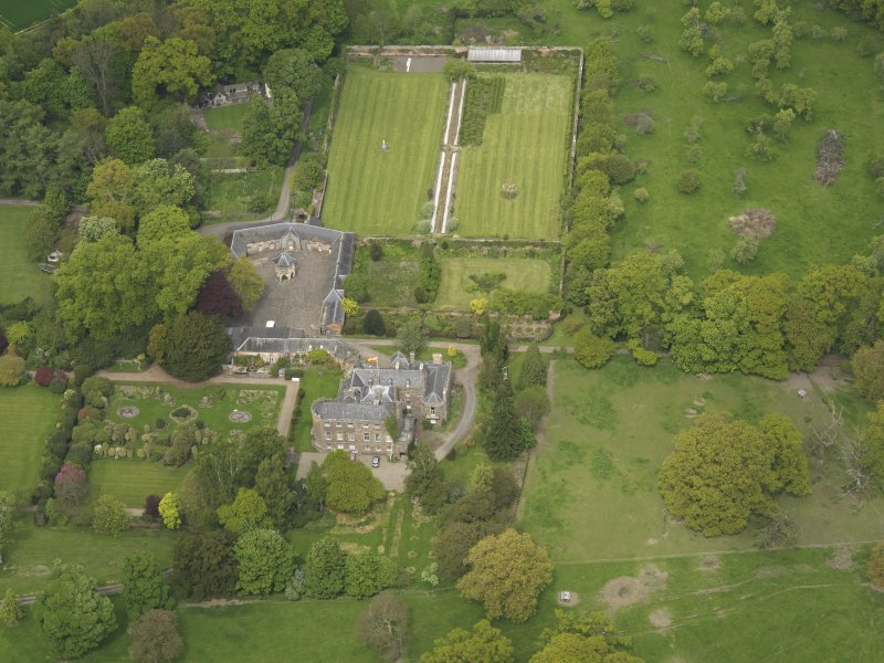 Oblique aerial view of the tower house with the gardens and stables adjacent, taken from the S.