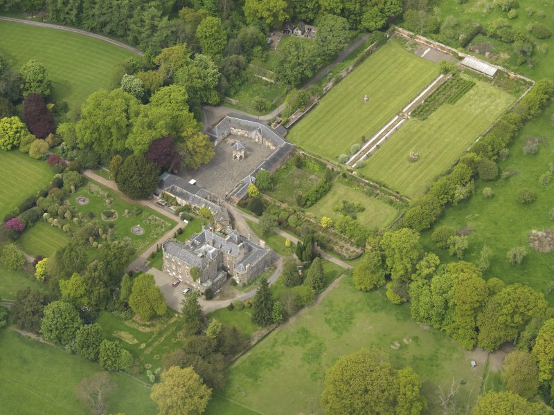 Oblique aerial view of the tower house with the gardens and stables adjacent, taken from the SSE.