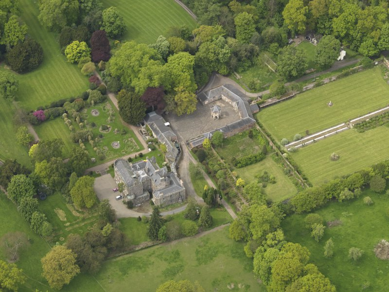 Oblique aerial view of the tower house with the gardens and stables adjacent, taken from the SE.