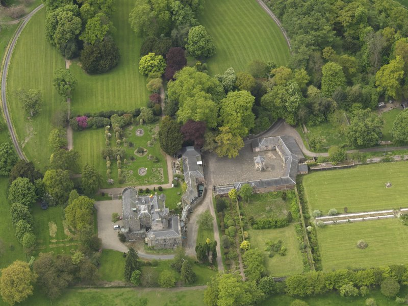 Oblique aerial view of the tower house with the gardens and stables adjacent, taken from the E.