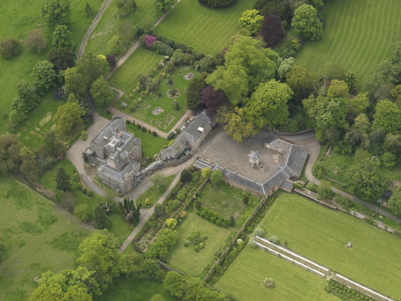 Oblique aerial view of the tower house with the gardens and stables adjacent, taken from the NE.