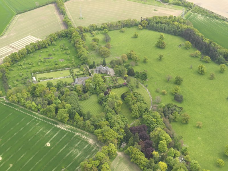 General oblique aerial view of the tower house with the gardens and stables adjacent, taken from the NW.
