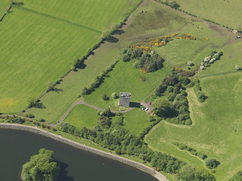 Oblique aerial view centred on the tower house with the remains of the motte (earthworks) adjacent, taken from the SSE.