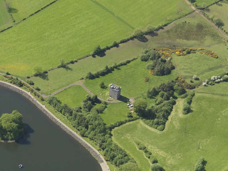 Oblique aerial view centred on the tower house with the remains of the motte (earthworks) adjacent, taken from the SE.