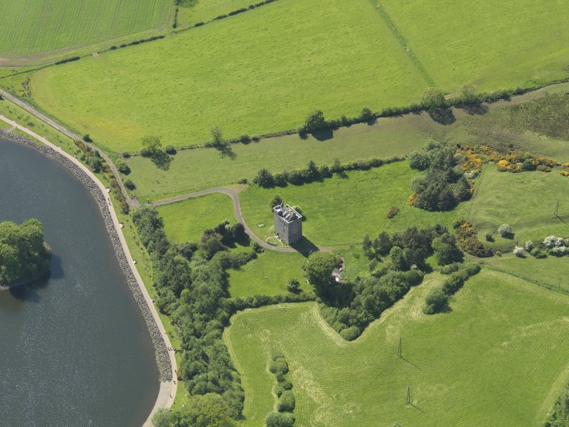 Oblique aerial view centred on the tower house with the remains of the motte (earthworks) adjacent, taken from the E.