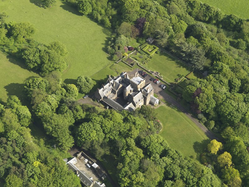 Oblique aerial view centred on the house with the terraced garden adjacent, taken from the NW.