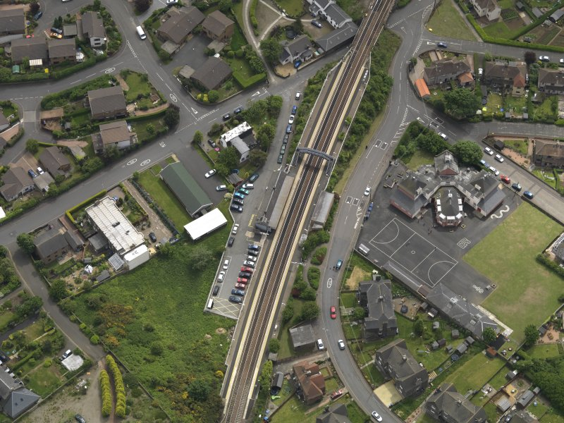 Oblique aerial view centred on the railway station with the school adjacent, taken from the SSE.