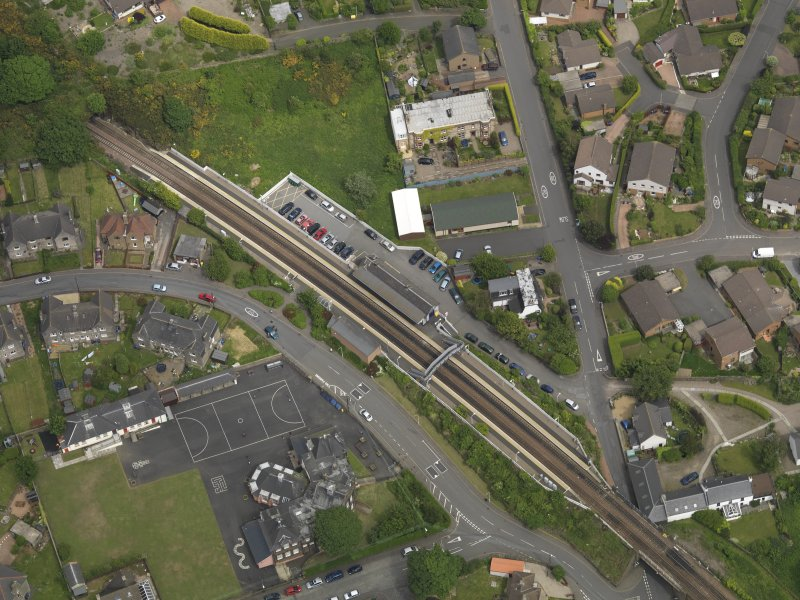 Oblique aerial view centred on the railway station with the school adjacent, taken from the SSW.
