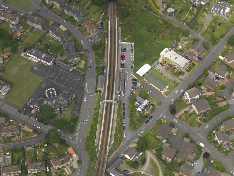 Oblique aerial view centred on the railway station with the school adjacent, taken from the S.
