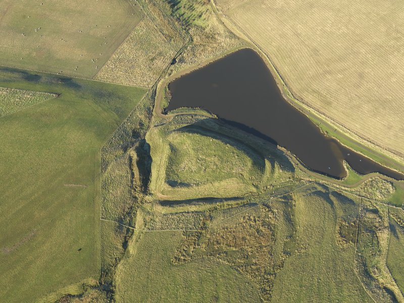 Oblique aerial view of the remains of Green Castle fort and rig, taken from the SE.
