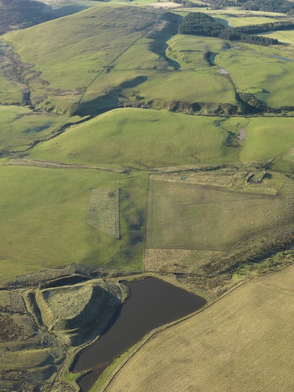 General oblique aerial view of the remains of Green Castle fort and rig in the foreground with Park Burn fort and rectilinear settlement in the distance, taken from the NE.
